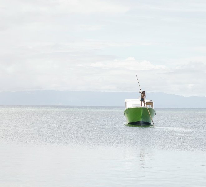A lone Indonesian boatman in his boat perching to shore in the c